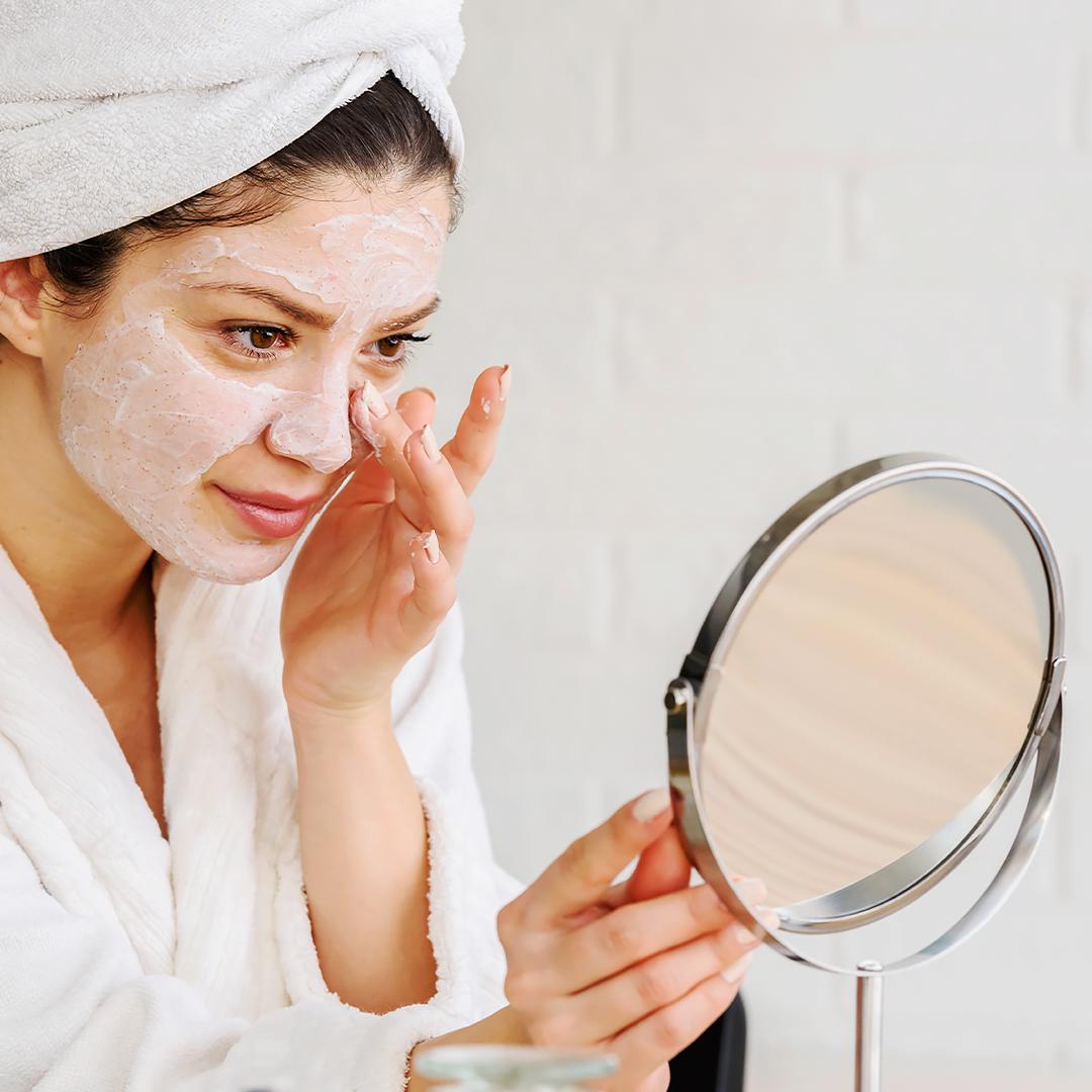Jak zmniejszyć nadmiar sebum - uśmiechnięta kobieta z maseczką na twarzy